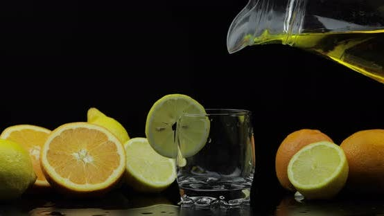 Thumbnail for Pour Juice From Pitcher Into Glass, Orange and Lemon Slices on Background