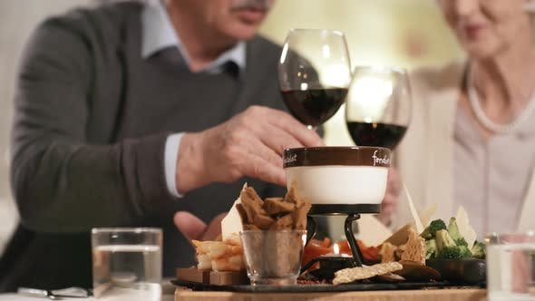 Thumbnail for Wealthy Elderly Couple Enjoying Wine and Fondue in Restaurant