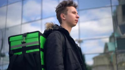 Delivery Man with Green Bagpack Walks Through the City with Food Delivery