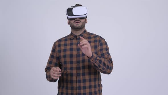 Cover Image for Young Bearded Indian Hipster Man Using Virtual Reality Headset