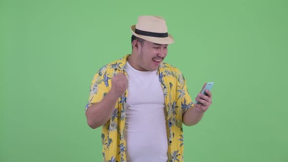Thumbnail for Happy Young Overweight Asian Tourist Man Using Phone and Getting Good News