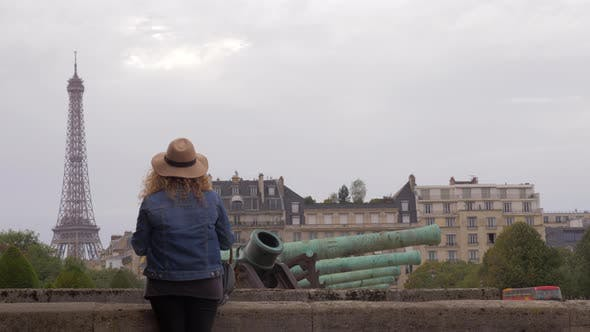 Woman tourist looking at Eiffel Tower from Les Invalides in Paris, France