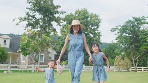 Asian family having fun together at home. Mother holding child hand walking outdoor in garden.