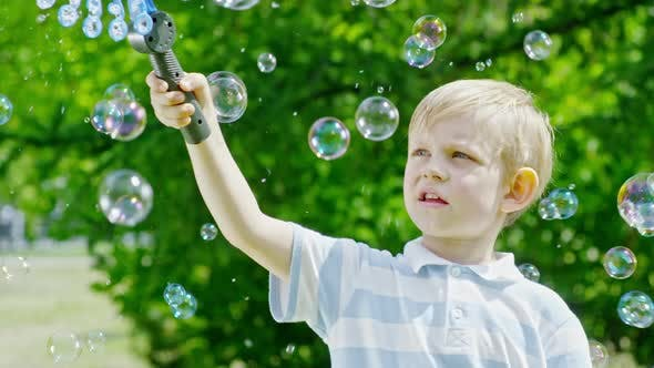 Thumbnail for Amazed Little Kid Blowing Lots of Bubbles Outdoor