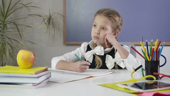 Thumbnail for Porträt von Ziemlich kaukasischen Mädchen sitzend Schreiben in Übungsbuch und Blick weg nachdenklich
