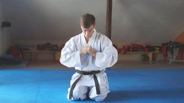 Thumbnail for Karate Man in Kimono Sits on Knees on Floor in Martial Arts Gym