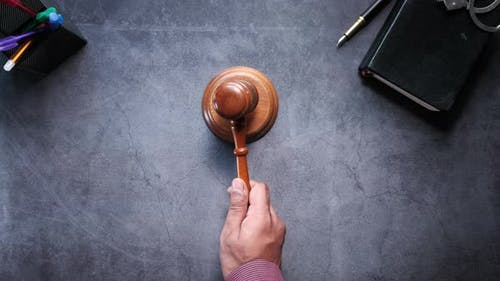 Top View of Judge Hitting Gavel Off on Black Background
