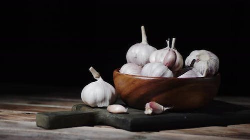 Garlic Cloves in a Bowl on the Cutting Board Slowly Rotate