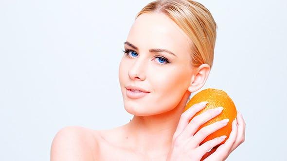 Thumbnail for Pretty Caucasian Blond Girl Holding Orange Fruit