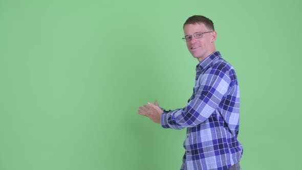 Thumbnail for Portrait of Happy Hipster Man Talking While Showing To Back