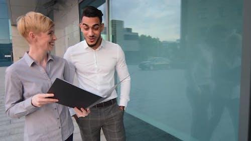 Caucasian Businesswoman and Arabic Hispanic Businessman Multiracial Colleagues Walking in Street