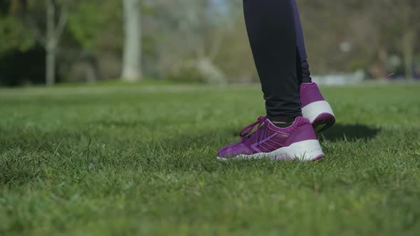 Thumbnail for Slim Female Legs in Black Leggings Walking on Grass in Park