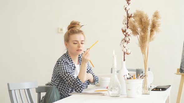 Beautiful Blond Girl with Bun in Stylish Casual Clothes Choosing a Pencil