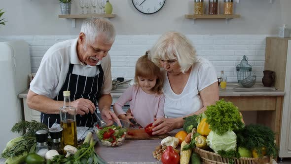 Thumbnail for Elderly Grandparents in Kitchen Teaching Grandchild Girl How To Cook Salad, Chopping Red Pepper