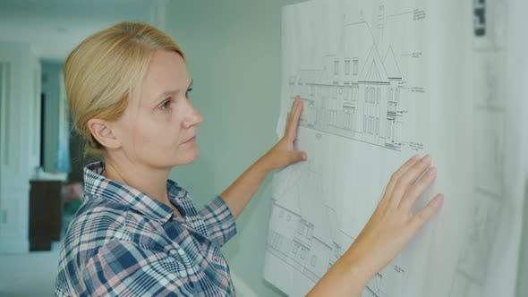 Thumbnail for Young Female Designer Looks at Drawing at Home