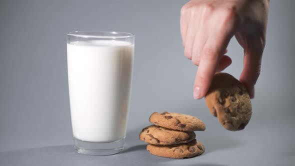 Hand Dipping a Cookie Into Glass of Milk
