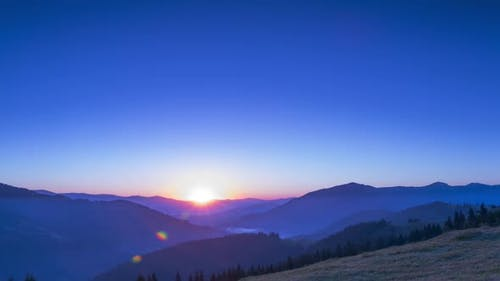 Sunrise in the Cloudless Sky over the Mountains