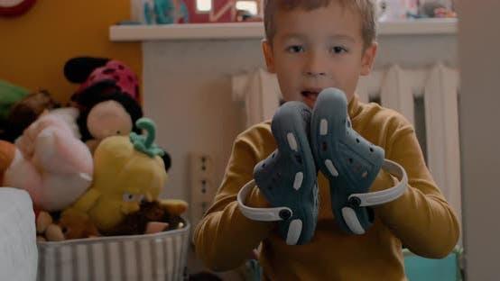 Garçon mettant des chaussures sur les mains et applaudissements