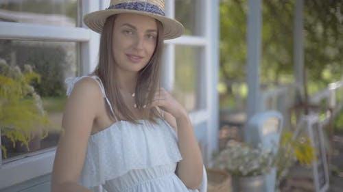 Belle jeune femme en paille chapeau regardant la caméra souriant heureux en plein air