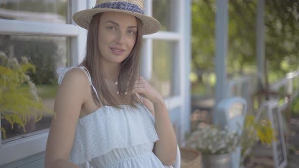 Schöne junge Frau in Strohhut Blick auf die Kamera Lächeln glücklich im Freien