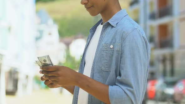 Teen Boy Counting Money Considering Purchase
