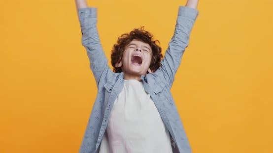 Kindergenuss. Happy Boy Genießen Sie Gewinn, Schreien mit erhobenen Händen