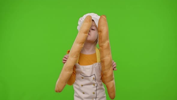 Child Girl Cook Chef Baker in Apron and Hat Sniffing Two Baguettes Fooling Around Dancing