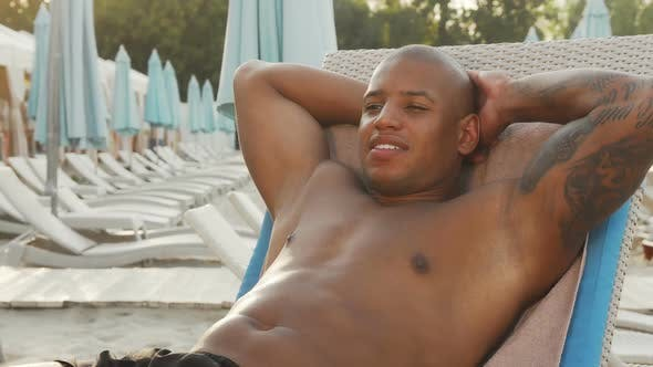 Thumbnail for Handsome African Man Sunbathing at the Beach