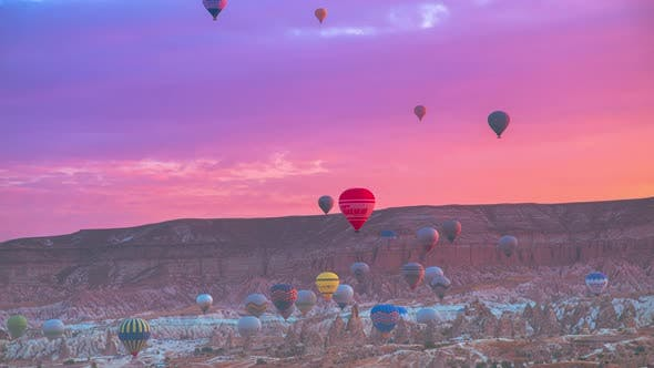 Landscape of Vibrant colorful balloons in pink sunrise in Goreme, Cappadocia, Turkey
