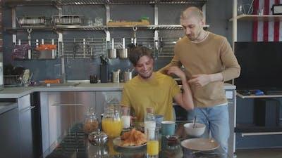 Happy Man Surprising Male Partner with Breakfast