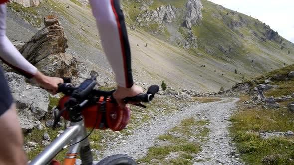 Thumbnail for A man mountain biking on a European mountainside biking trail.