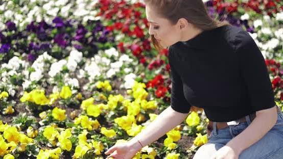 Thumbnail for Side View of Female in Casual Outfit Sitting on Side of Flowerbed