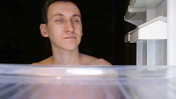 Yawning Guy Opens Unfilled Refrigerator To Find Food Closeup