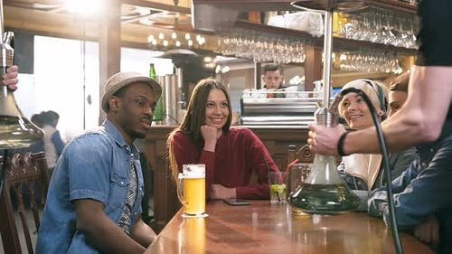 Group of Young Friends Chatting in the Bar, Pub
