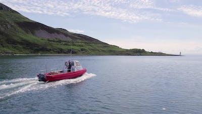 A Small Cargo Ferry at Sea Motoring Alongside an Island
