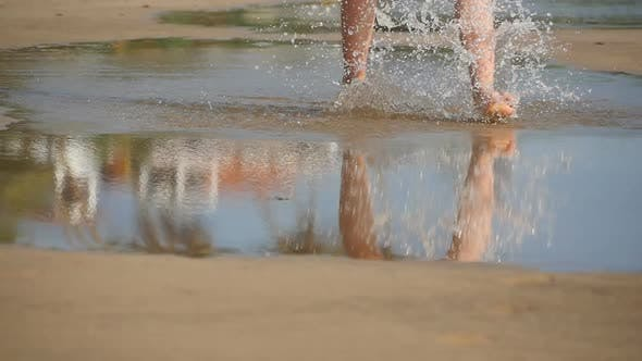 Low View of Female Legs Steps Into Big Puddle of Ocean Water Near Seashore. Bare Feet of Young Woman