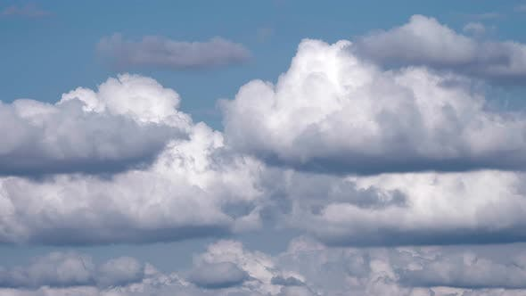 Time lapse of white fluffy clouds over blue sky.