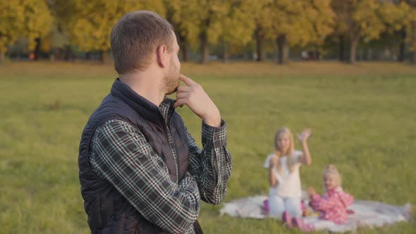 Thumbnail for Thoughtful Caucasian Man Waving To His Daughters on the Background and Looking at the Camera