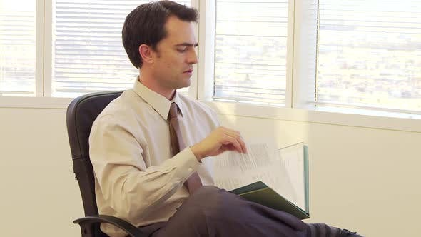 Thumbnail for Businessman looking through paperwork files