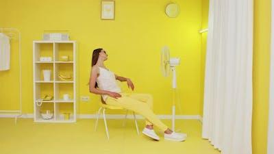 Beautiful Model Is Posing On Chair In Front of Electric Fan