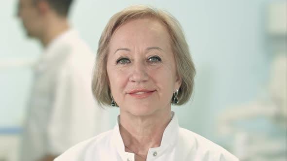 Smiling senior female doctor looking at camera