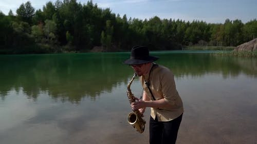 a Musician in a Hat Plays a Saxophone in Nature, Standing on the Shore of a Quiet Forest Lake on a