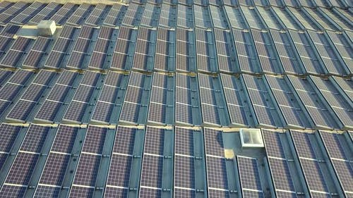 Aerial View of Many Photo Voltaic Solar Panels Mounted of Industrial Building Roof