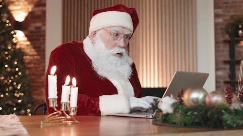 Amused Santa Using Laptop Computer