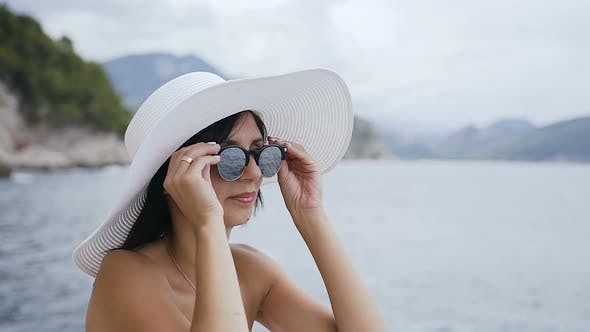 Cute Girl in Sunglasses and Hat on the Beach