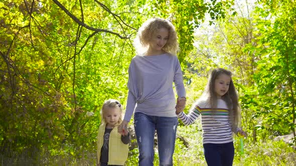 Thumbnail for Happy Caucasian Family Walking Between the Trees in the Autumn Park