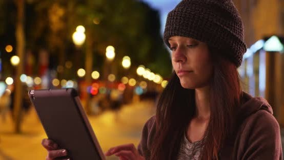 Thumbnail for Smiling woman using tablet computer on Champs Elysees at night