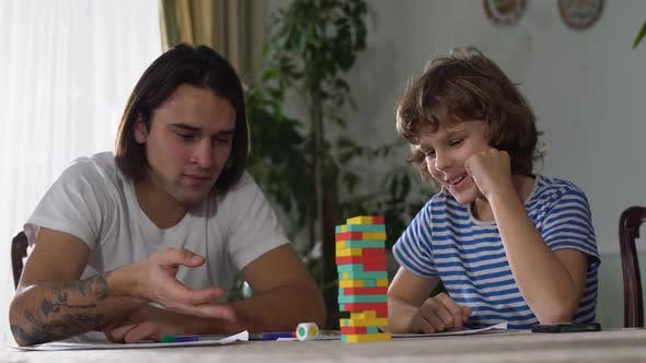 Thumbnail for Two Brother, One Young and One Adult, Play Game on the Table and Having Fun. Brothers Relationship