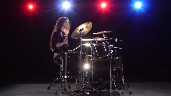 Thumbnail for Girl Drummer with Chopsticks Beats Rhythmic Music. Black Background . Red Light Blue. Side View