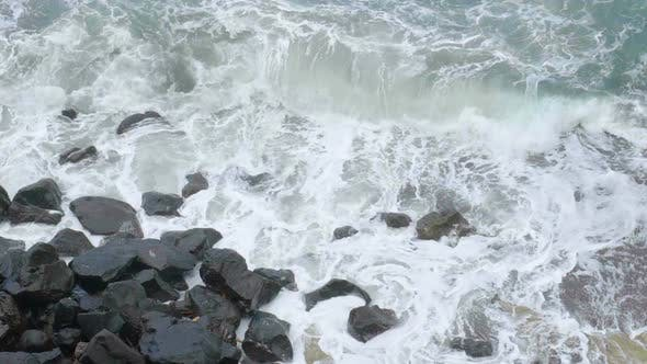 Stormy Sea with Foamy Waves Breaking in Splashes Against Cliff, Slow Motion
